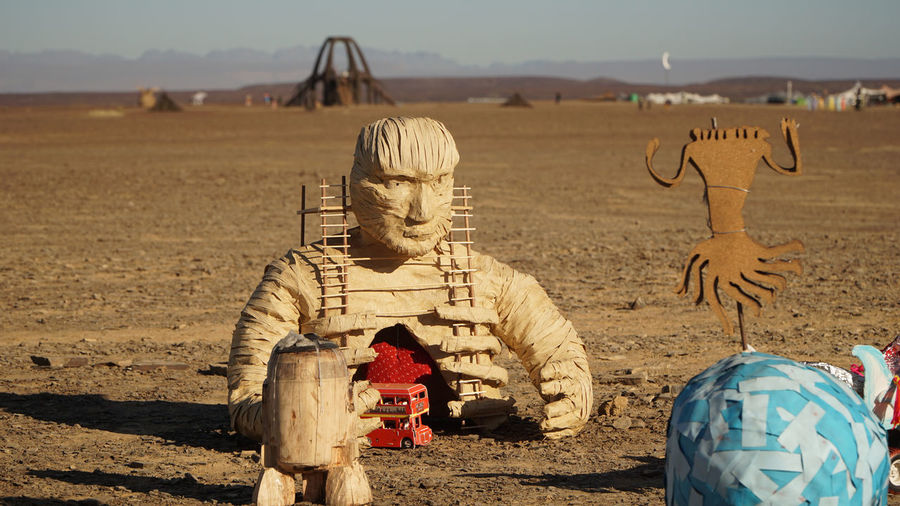 Traditional sculpture on field against sky