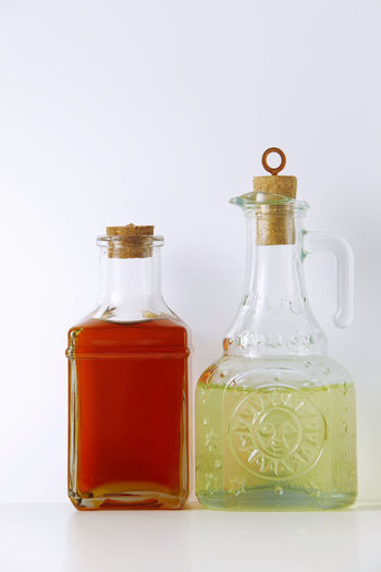 Close-up of oil in bottles on table against white background