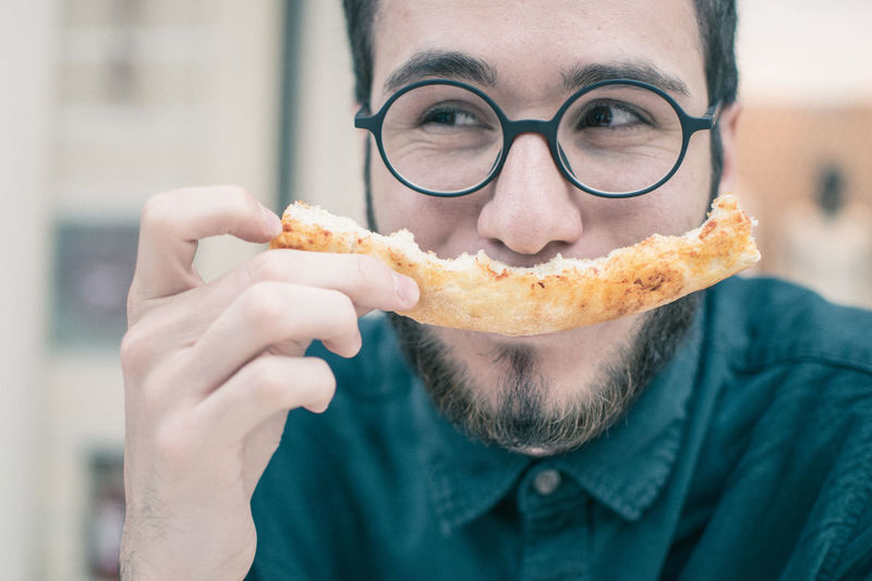 Close-up of smiling of man having pizza