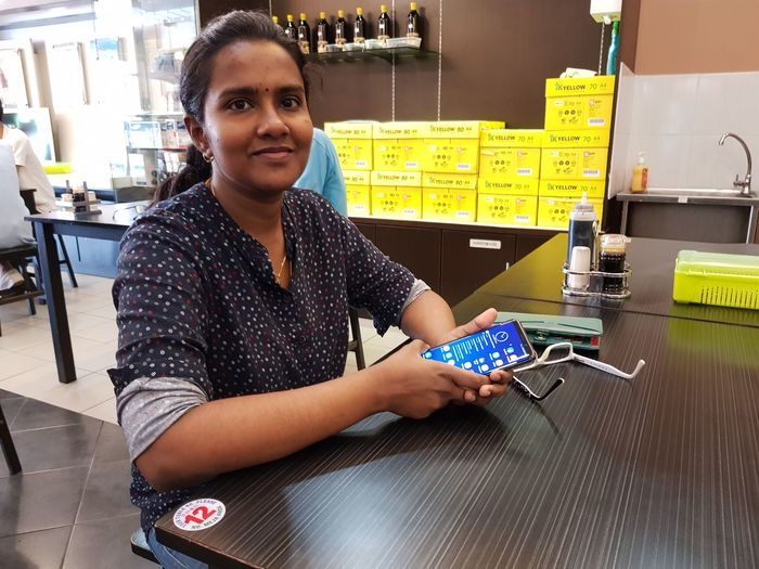 Portrait Of Young Woman Using Mobile Phone While Sitting At Wooden Table In Cafe