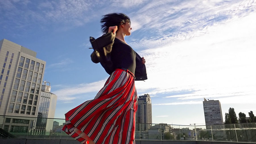 Low angle view of young woman standing in city against sky