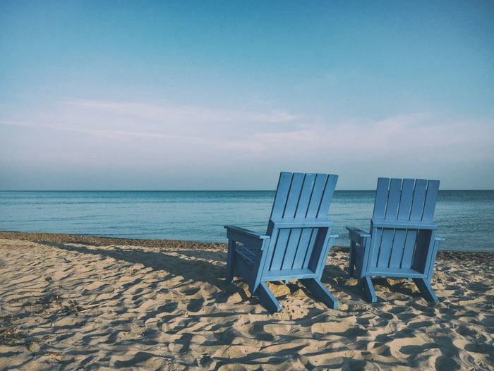 Outdoor chairs on sand against sea at beach