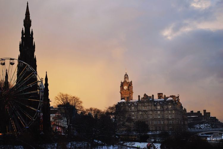 Silhouette edinburgh cathedral by clock tower in city against sky during sunset