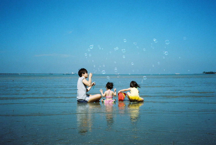 Family Sitting At Beach Against Clear Blue Sky During Sunny Day