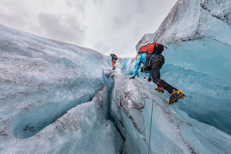People climbing on frozen mountain