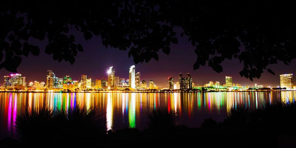 Nestled in a little park in between two multi-million dollar homes, this location is often missed by tourists. It is indeed our very own Hidden Gems  ! Bayview Park, Coronado CA 92118 It features a couple of benches set under a tree overlooking the San Diego skyline, the bay, and several other attractions. San Diego Coronado California Night Skyline Lights Building Architecture Bay Water Ocean Sky Stars Tree Bench Silhouette City Tranquility Relaxing Calm