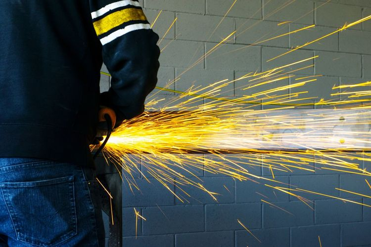 Midsection Of Man Working Welding In Factory