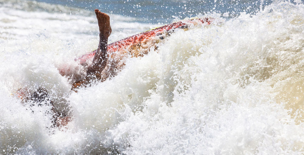 Waves Over Person Surfboarding On Sea