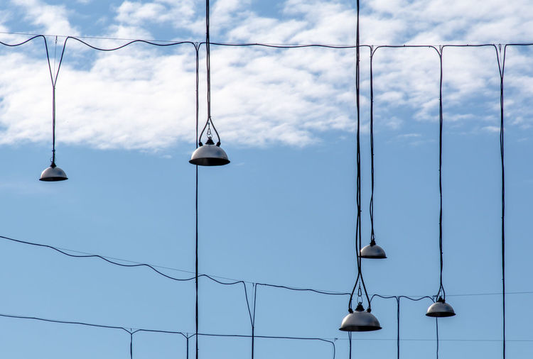 Low angle view of hanging lamps against sky