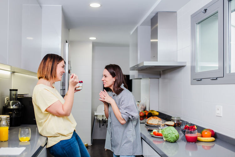 Cheerful women talking while standing in kitchen
