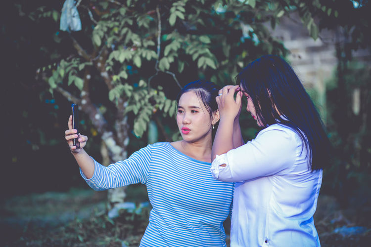 Young woman photographing while standing on mobile phone