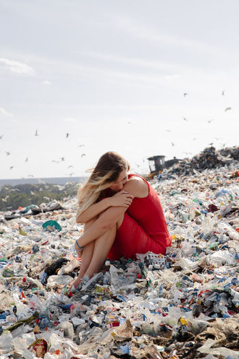 Woman sitting amidst garbage against sky