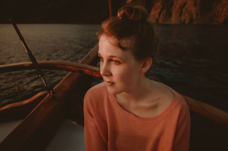 Girl sitting on boat in sea