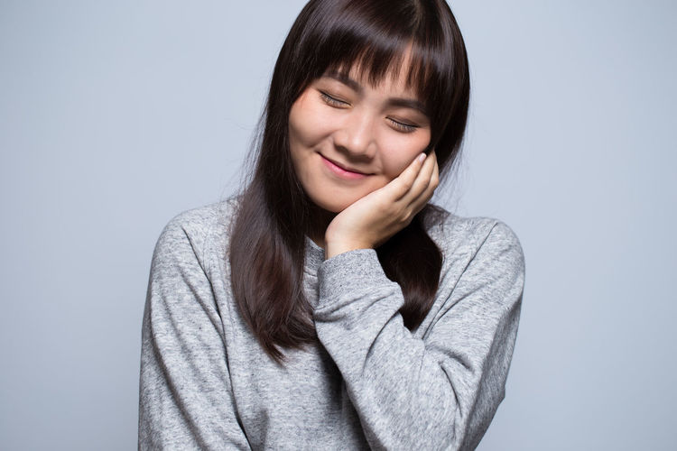Smiling Young Woman Against Gray Background