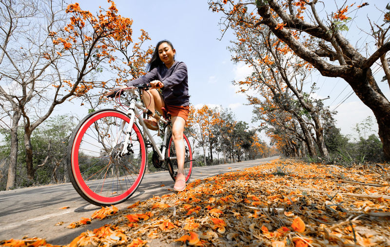 Young woman riding bicycle on autumn leaves