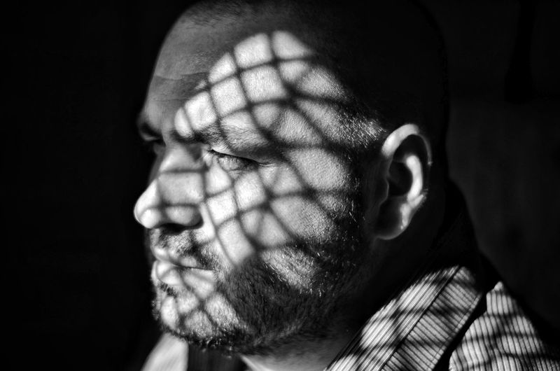 Sunlight Falling On Thoughtful Man In Darkroom