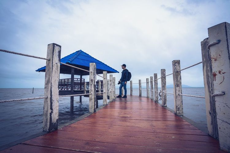 Side view of man standing on pier over sea against cloudy sky
