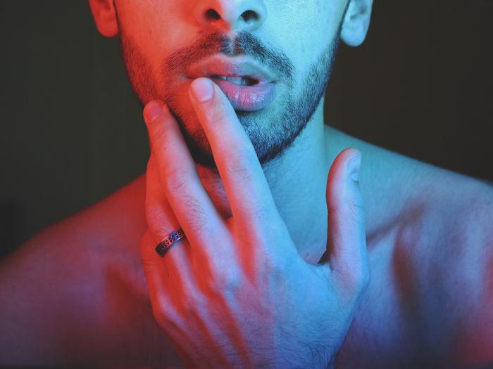 Close-up portrait of man making face against black background
