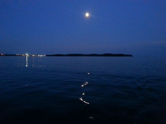 Hazy moon's silvery reflection on the water during an evening cruise. Moon Moonlight Harbour Cruise Tall Ship Taking Photos Serenity