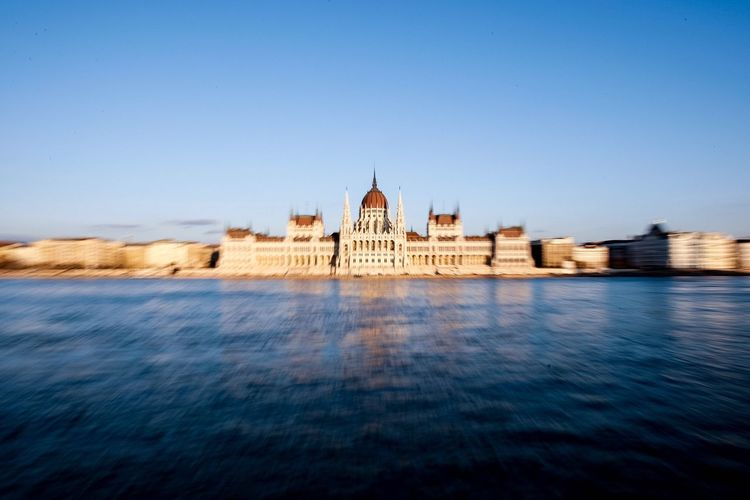 Hungarian parliament building by danube river against clear blue sky in city