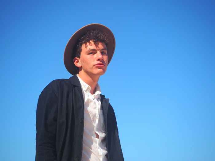 Low Angle Portrait Of Young Man Wearing Hat Standing Against Clear Blue Sky