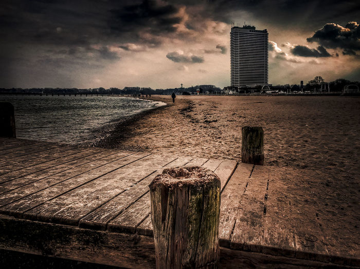 Wooden posts on river by buildings against sky