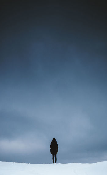 Low angle view of silhouette standing against sky
