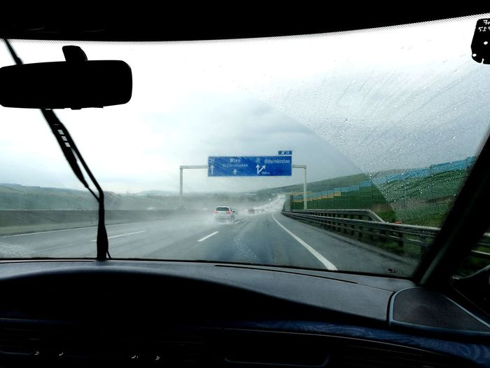 Cars on road against sky seen through car windshield