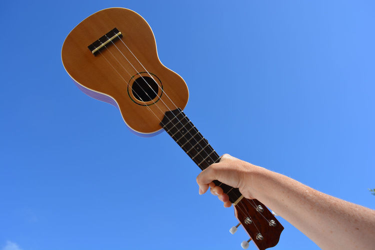 Cropped hand of woman holding ukulele against blue sky