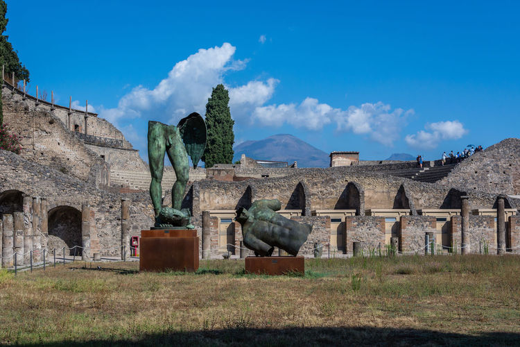 Broken Angel Sculpture Against Historic Building At Pompeii