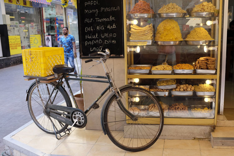 Delivery bike outside an Indian fritters and noodle shop. Delivery Bike Delivery Service Indian Culture  Sidewalk Bicycle Display Cabinet Food And Drink Indian Food Lassi Love Is Love Mung No People Papadam Retail Display Store Sweet Food Transportation
