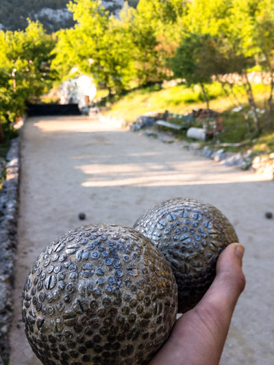 Man playing on bocce on outdoor court in Italy Balls Bocce Boccia Bowl Bowling Close-up Court Day Focus On Foreground Game Holding Human Hand IT Mediterranean  One Person Outdoor Outdoors People Play Playing Real People Recreational Pursuit Sport