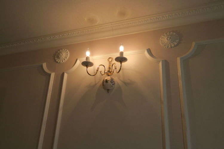 Low angle view of illuminated lighting equipment attached on wall