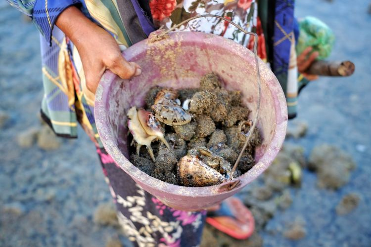 Low section of woman holding a bucket of clams