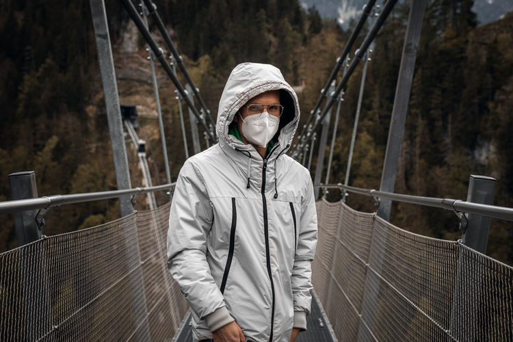 Traveler wears ffp2 medical face mask on pedestrian suspension bridge highline 179