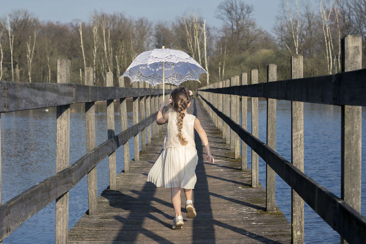 Portrait of girl with umbrella walking over water