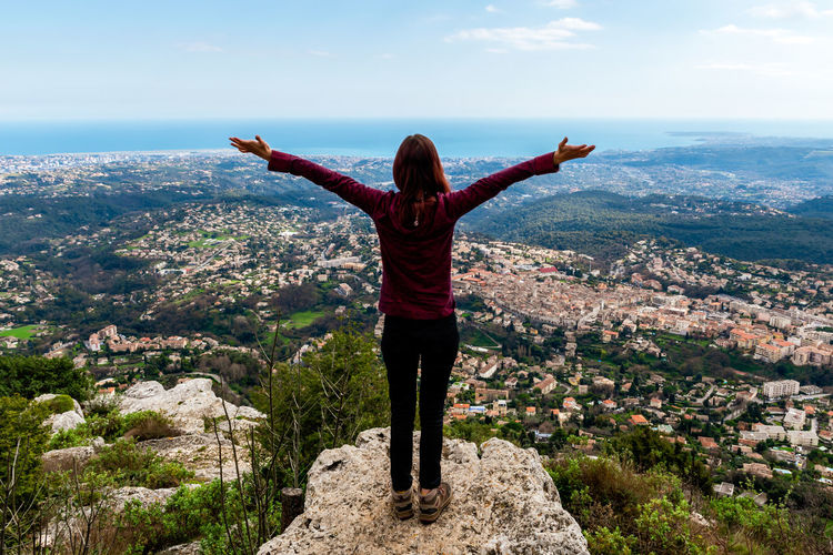 Rear view of woman with arms outstretched standing on cliff against sky