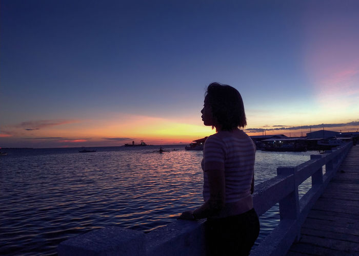 Rear view of woman looking at sea against sky during sunset