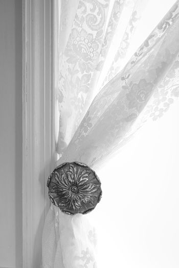 Close-up of decoration hanging against white wall
