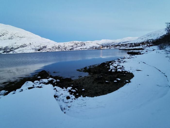 Scenic view of frozen lake by snowcapped mountain against sky
