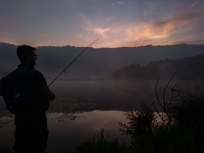 Activity Beauty In Nature Cloud - Sky Fisherman Fishing Fishing Rod Lake Nature Non-urban Scene One Person Outdoors Real People Rod Scenics - Nature Silhouette Sky Standing Sunset Tranquil Scene Tranquility Water