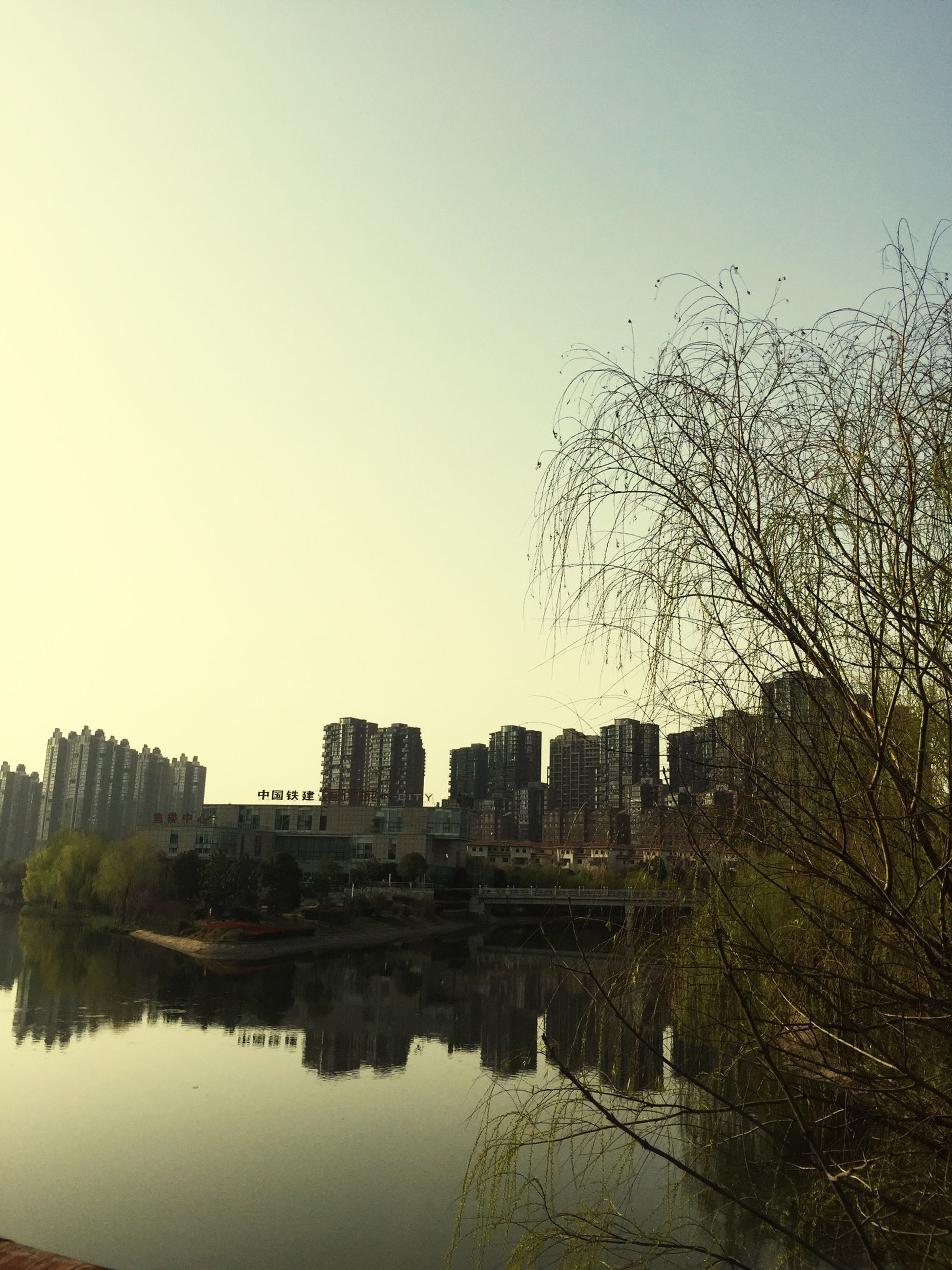 architecture, building exterior, built structure, water, reflection, clear sky, waterfront, tree, river, city, lake, copy space, building, sky, bare tree, residential building, residential structure, outdoors, day, no people