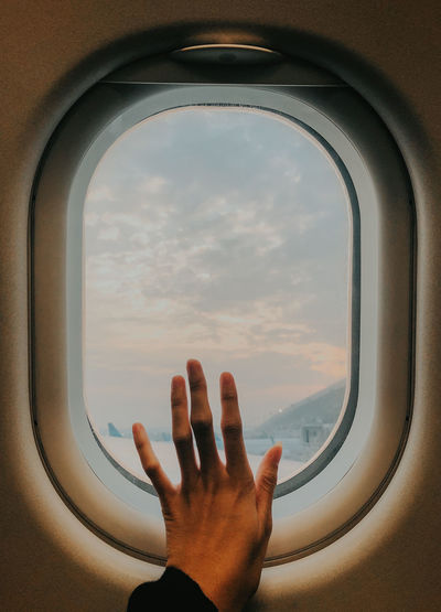 Cropped image of hand against sky seen through airplane window