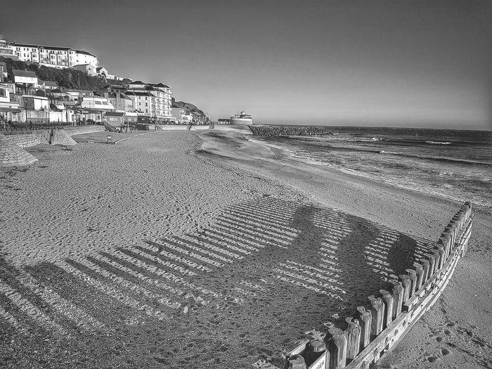 Shadow of groynes on sand at beach