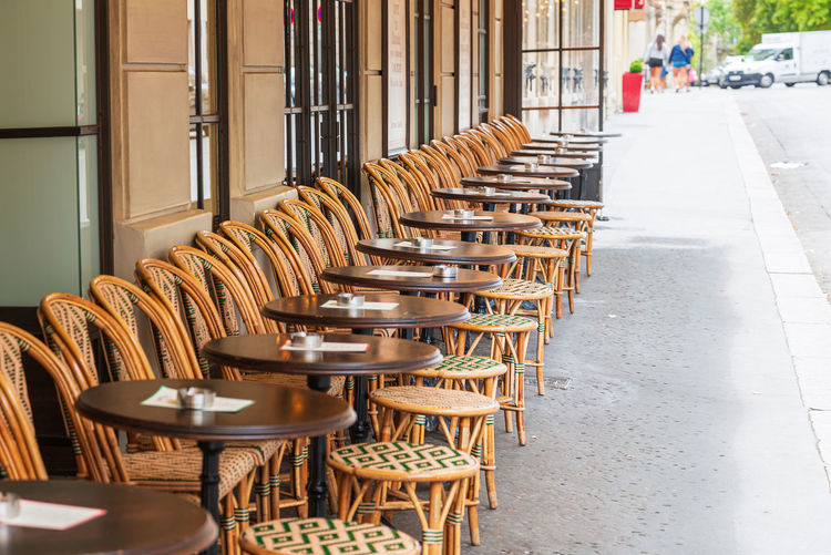 Empty chairs and tables in cafe outdoors