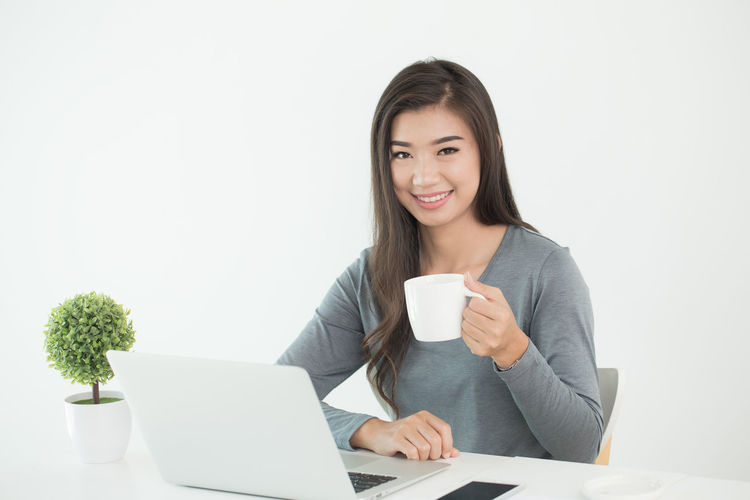 Asian women sit in office with coffee Asian  Sitting Business Office Female Coffee Young Girl Woman Beautiful person People Laptop Portrait Computer Businesswoman Lifestyle Work Happy Professional Table Adult Entrepreneur Technology Smile Looking Communication Modern Restaurant Attractive Internet Lady Desk Casual Home Relax Women Using Pretty ASIA Cup Room Online  Notebook One Person Smiling Young Women Holding Drink