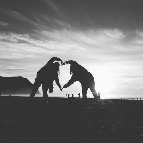 Two women making a heart shape on beach