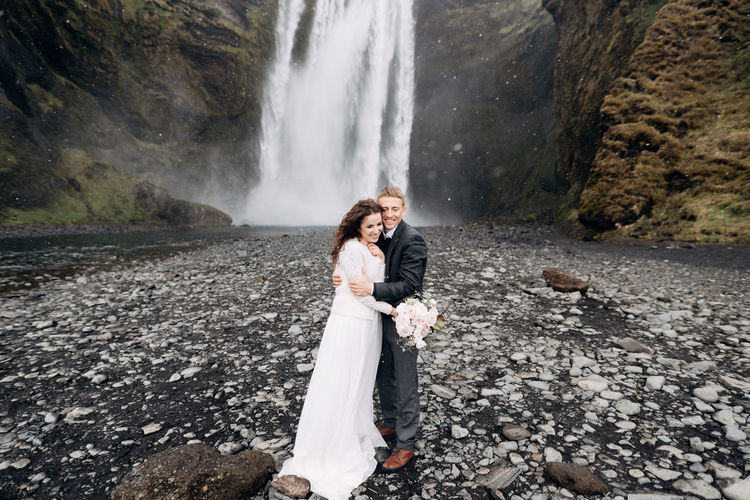 Couple standing on rock against waterfall
