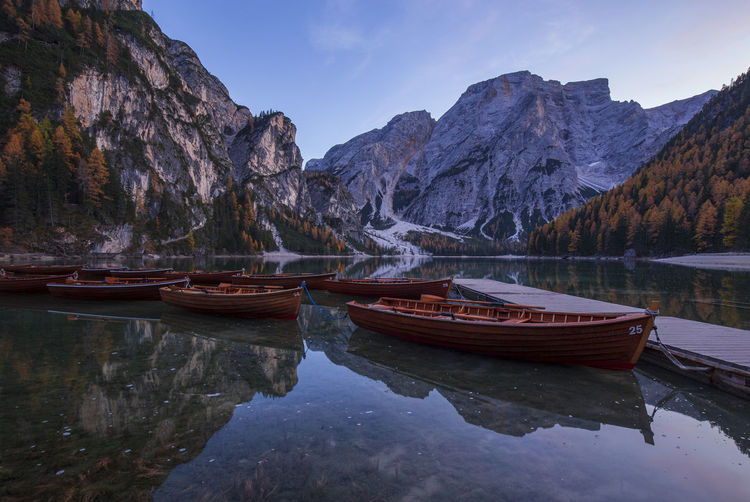 Boats moored in lake by mountains against sky at lago di braies in dolomites mountains