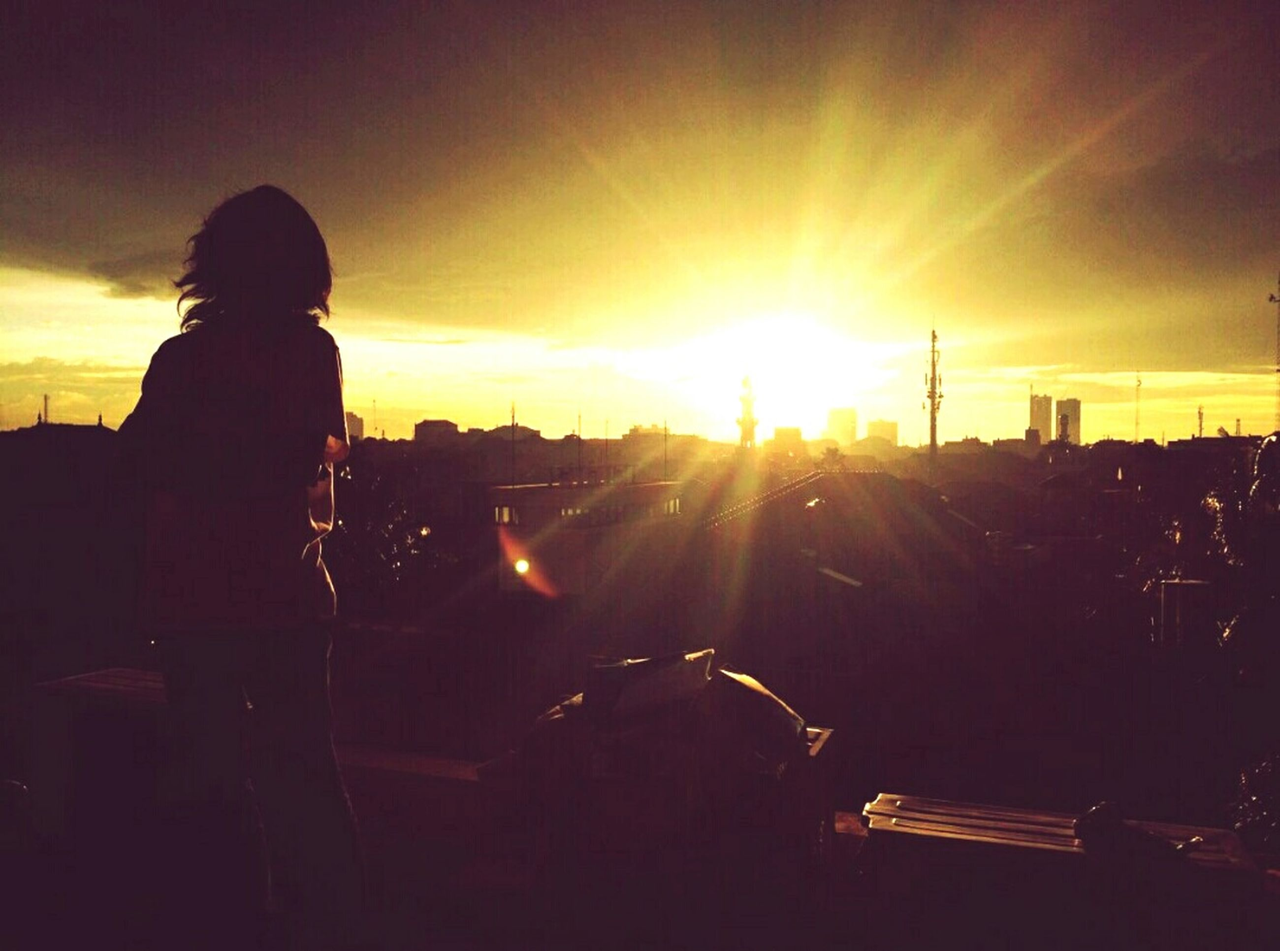 sunset, real people, sunlight, transportation, one person, sun, silhouette, rear view, sky, standing, lifestyles, outdoors, nature, day, people